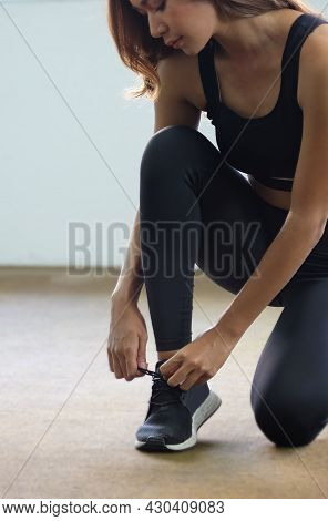 Fitness Woman Tying Shoelaces On Sneakers In The Gym.