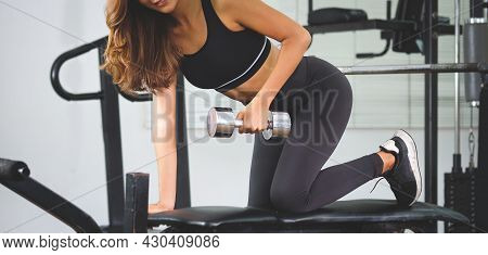 Young Sportswoman In Sportswear  Exercising With Dumbbells.