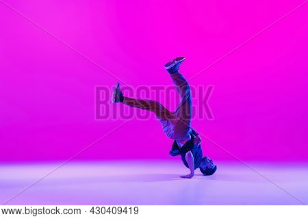 Young Stylish Man, Hip-hop Dancer Dancing Solo In Modern Clothes Isolated Over Bright Magenta Backgr