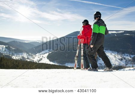 Young happy couple looking in snowy mountains holding ski. Winter sport vacation