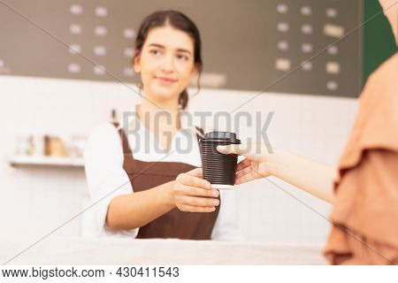 Takeaway Coffee Cup In Two Hands Of Customer And Beautiful Caucasian Barista Woman Who Looks At Othe