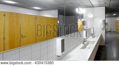 Interior Of A Public Restroom With Sinks, Faucets And Toilet Cubicles