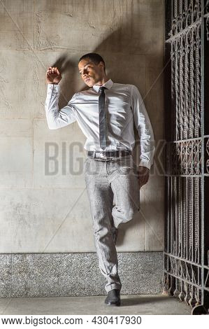 A Young Handsome Black Businessman Is Standing Outside A Gate And Into Deeply Thinking.