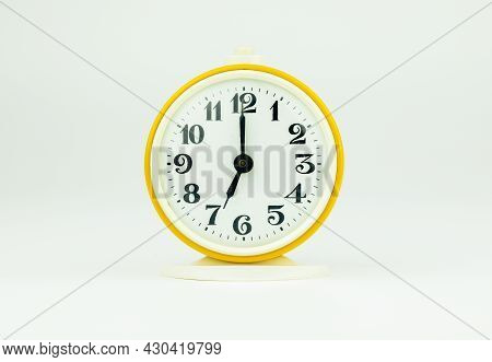 Alarm Clock Yellow Shows The Time 19 O'clock On A White Isolated Background