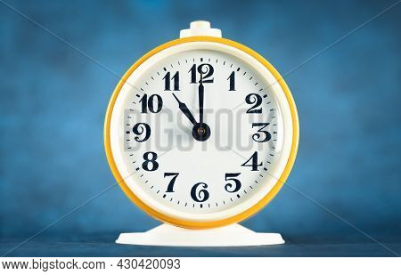 Yellow Alarm Clock Shows Time 11 O'clock On Blue Isolated Background