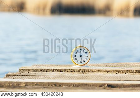 Old Alarm Clock On A Wooden Bridge Shows The Time 18 O'clock