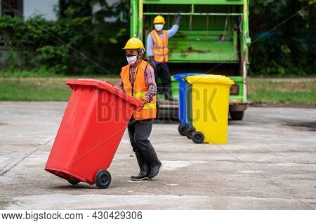 Rubbish Cleaner Man Working With Truck Loading Waste And Trash Bin.
