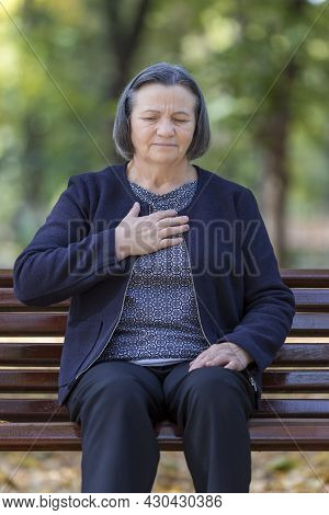 Aging Woman Having Heart Attack. Senior Lady Clutching Her Chest In Pain At The First Signs Of Angin