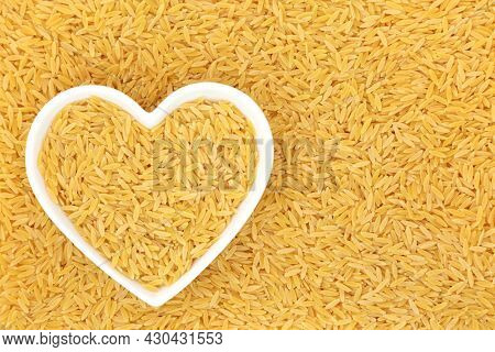 Orzo pasta health food in a heart shaped dish. Suitable for vegan,  vegetarian diet, gluten free, high in fibre, vitamins, minerals. Flat lay, top view.