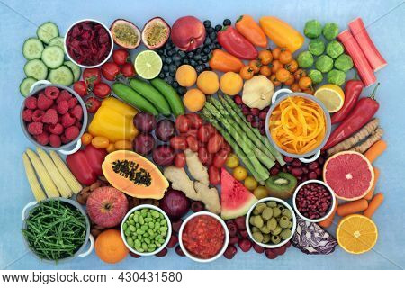 Antioxidant health foods that neutralize free radicals with fruit,  vegetables high in fibre, anthocyanins, lycopene, protein, vitamins, minerals, carotenoids. Healthy food concept. On mottled blue.