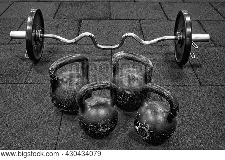 Bar And Kettlebell Weights On Rubber Floor Ready For Strength And Conditioning Workout.