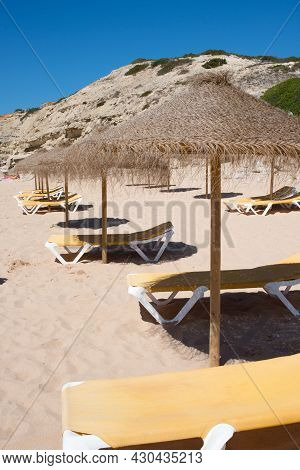 Sunshades And Yellow Deck Chairs In A Row With No People. Algarve, Portugal, Europe