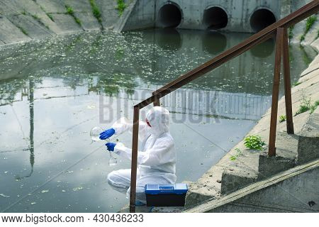 Sampling From Open Water. A Scientist Or Biologist Takes A Water Sample Near An Industrial Plant. Wa