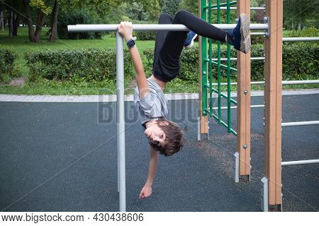 Boy Doing Exercise Upside Down On Crossbeams On Outdoor Playground Against The Backdrop Of Green Bus