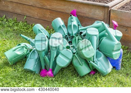 Plastic Watering Cans Piled In A Heap In The Garden