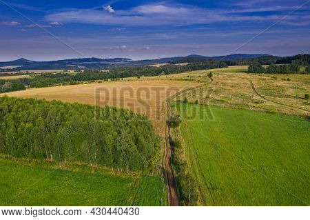 Sudeten Foothills. Undulating Terrain Covered With Arable Fields, Meadows, Clumps Of Trees. In The D