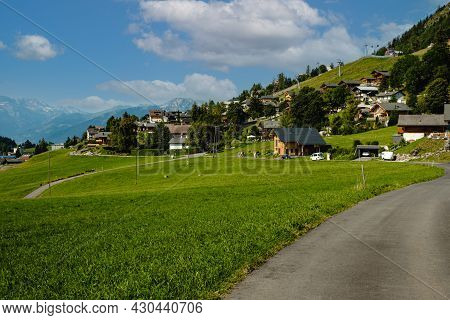 Concrete Mountain Road And Green Alpine Pastures In The Swiss Municipality Leysin In The Canton Of V