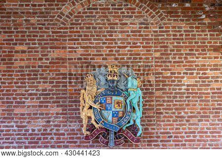 Jamestowne, Va, Usa - April 1, 2013: Historic Site. English Royal Coat Of Arms Against Red Brick Wal