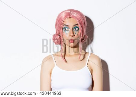 Image Of Beautiful Silly Girl In Pink Wig, With Bright Makeup, Pouting And Looking Interested Left,