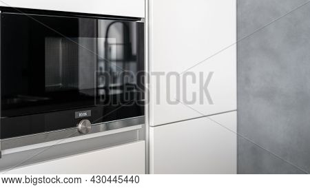 Spacious White Cupboard With Built-in Glossy Black Microwave Oven, Control Knob To Adjust Power And