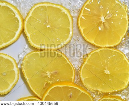 Lemon Close-up In Liquid With Bubbles. Slices Of Yellow Ripe Lemon In Water. Close-up Fresh Slices O