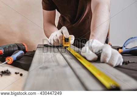 Repair, Building And Home Concept - Close Up Of Male Hands Measuring Wood Boards. Professional Carpe