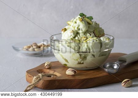 Pistachio Ice Cream With Nuts In Transparent Glass Ice-cream Bowl On A Light Gray Background.