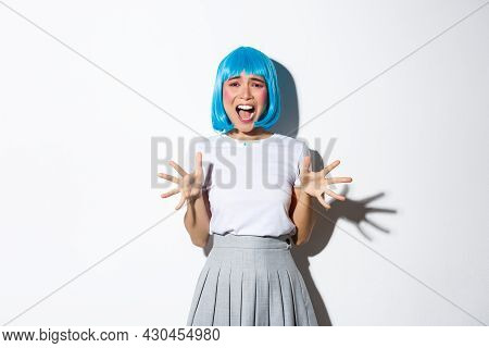 Portrait Of Asian Girl Wearing Blue Wig As A Costume For Halloween, Screaming From Fear, Looking Hor