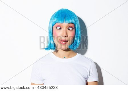 Close-up Of Funny And Silly Asian Girl Entertainer Celebrating Halloween, Wearing Blue Wig And Squin