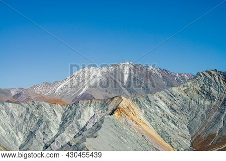 Multicolor Autumn Landscape With Snow-covered Mountain Peak And Gray Rockies With Orange And Lilac T