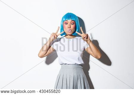 Silly And Funny Asian Girl Blowing Bubble Gum, Showing Peace Gestures, Standing In Blue Short Wig An