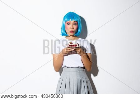 Portrait Of Surprised Silly Asian Girl Looking Coquettish At Camera, Holding Cake On Plate, Wearing