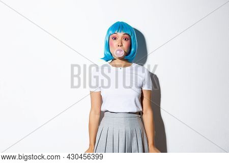 Beautiful Asian Girl In Blue Wig And Schoolgirl Costume, Blowing Bubble Gym With Silly Face, Dressed
