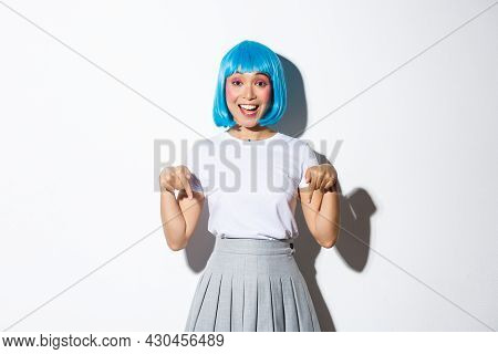 Image Of Happy Silly Asian Girl Showing You Logo Or Product Advertisement, Pointing Fingers Down And