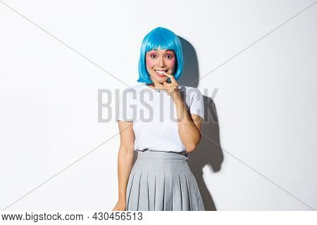 Portrait Of Silly Asian Girl In Blue Wig, Smiling And Looking Curious, Standing Over White Backgroun