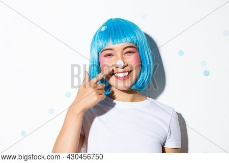 Image Of Cute And Silly Asian Girl With Confetti On Her Nose Smiling And Looking Happy, Wearing Blue