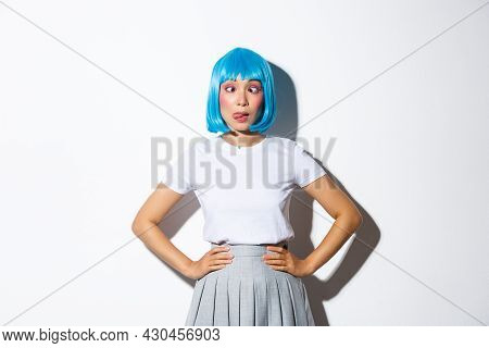 Portrait Of Silly Asian Girl In Blue Wig And Party Outfit Showing Tongue, Squinting And Making Funny