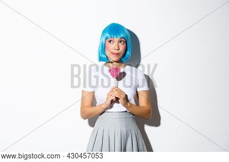 Image Of Silly Asian Girl In Blue Wig, Dressed-up For Halloween Party, Looking Dreamy At Upper Left