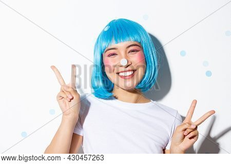 Image Of Cute And Silly Asian Girl With Confetti On Her Nose Smiling Happy And Showing Peace Gesture