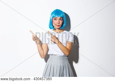 Intrigued Silly Asian Girl With Rouge Cheeks And Kawaii Blue Wig, Looking At Upper Left Corner And P