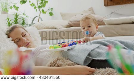 Tired Mom Fell Asleep While Her Child Baby Son Plays With Colorful Educational Learning Toy, Lying A
