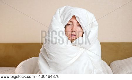 Upset Young Frozen Woman Wrapped With Soft White Duvet Sits On Large Bed In Cold Room During Turning