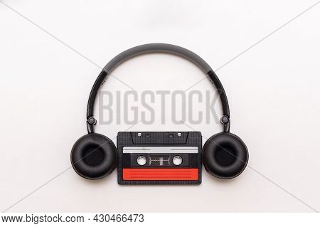 On-ear Black Headphones And Old Analog Magnetic Cassette Isolated On White Background, Close-up.