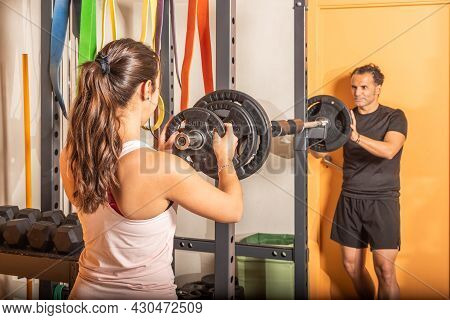 Man And Woman Putting Weight Plate On Bar In Gym