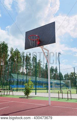 Street Sport Concept. Basketball Backboard With A Basket Made Of Iron Chains On A Sunny Day. Vertica
