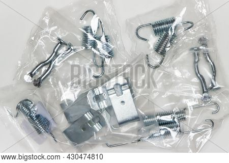 A Set Of Metal Components In The Package, Parts For Car Repair. A Set Of Spare Parts For Servicing V