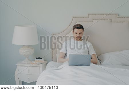 Attractive Young European Man Watching Video Online On Portable Laptop Computer While Sitting In Com
