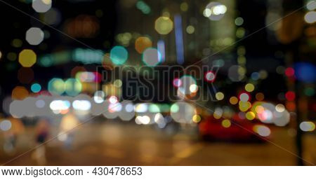 Image of road traffic in city at night with blurred city lights and colourful spots of light in the foreground 4k