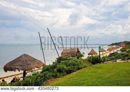 Scenic View Of Tulum Beach With Sunshades On Coast Against Cloudy Sky