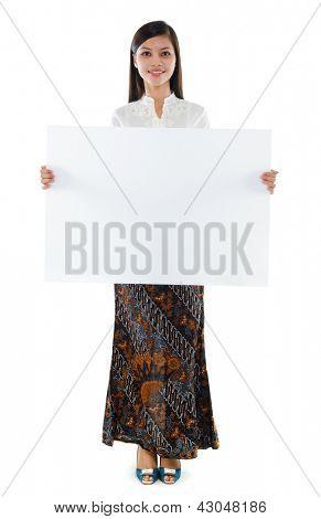 Todo o corpo atraente Sudeste Asiático jovem mulher em traje de batik tradicional kebaya segurando um branco